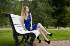 Schönes blondes Mädchen im blauen Kleid, das auf einer Bank im Sommer sitzt Stockfotos