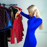 Schönes blondes Mädchen im blauen Kleid, das ein Hemd in der Kleidung wählt Stockfotografie