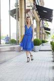 Schönes blondes Mädchen im blauen Kleid, das gegen einen Hintergrund aufwirft Lizenzfreie Stockfotos