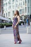 Schönes blondes Mädchen im blauen Kleid, das gegen einen Hintergrund aufwirft Stockbilder
