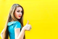 Schönes blondes Mädchen im blauen Kleid, das sich Finger zeigt Lizenzfreies Stockfoto