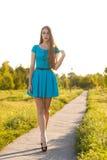 Schönes blondes Mädchen im blauen Kleid gehend auf eine Straße in einem Park Lizenzfreies Stockbild