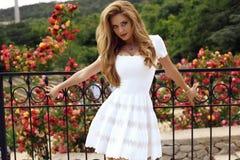 Schönes blondes Mädchen im eleganten Kleid, das im Sommerpark aufwirft Lizenzfreies Stockfoto