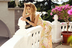 Schönes blondes Mädchen im eleganten Kleid, das im Sommerpark aufwirft Stockfotos