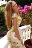 Schönes blondes Mädchen im eleganten Kleid, das im Sommerpark aufwirft Stockbild