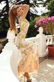 Schönes blondes Mädchen im eleganten Kleid, das im Sommerpark aufwirft Lizenzfreies Stockbild