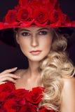 Schönes blondes Mädchen im Kleid und im Hut mit Rosen, klassisches Make-up, Locken, rote Lippen Schönes lächelndes Mädchen Lizenzfreies Stockbild