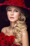 Schönes blondes Mädchen im Kleid und im Hut mit Rosen, klassisches Make-up, Locken, rote Lippen Schönes lächelndes Mädchen Lizenzfreie Stockbilder