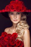 Schönes blondes Mädchen im Kleid und im Hut mit Rosen, klassisches Make-up, Locken, rote Lippen Schönes lächelndes Mädchen Stockbild
