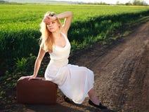 Schönes blondes Mädchen im langen weißen Kleid, sitzend auf Koffer stockfotos