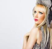 Schönes blondes Mädchen im Pelzhut auf grauem Hintergrund Lizenzfreie Stockfotos