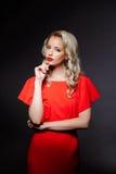 Schönes blondes Mädchen im roten Abendkleid über grauem Hintergrund Stockfotografie