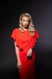 Schönes blondes Mädchen im roten Abendkleid über grauem Hintergrund Lizenzfreie Stockfotos