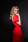 Schönes blondes Mädchen im roten Abendkleid über grauem Hintergrund Lizenzfreie Stockbilder