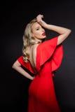 Schönes blondes Mädchen im roten Abendkleid über grauem Hintergrund Stockfotos