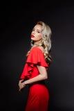 Schönes blondes Mädchen im roten Abendkleid über grauem Hintergrund Lizenzfreie Stockfotografie