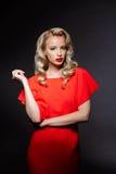 Schönes blondes Mädchen im roten Abendkleid über grauem Hintergrund Stockbild