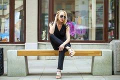 Schönes blondes Mädchen im schwarzen Kleid, das auf einer Bank im summe sitzt Lizenzfreie Stockfotos