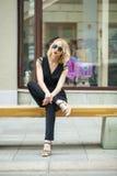 Schönes blondes Mädchen im schwarzen Kleid, das auf einer Bank im summe sitzt Stockbild