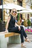 Schönes blondes Mädchen im schwarzen Kleid, das auf einer Bank im summe sitzt Stockfotografie