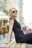 Schönes blondes Mädchen im schwarzen Kleid, das auf einer Bank im summe sitzt Stockbilder