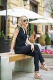 Schönes blondes Mädchen im schwarzen Kleid, das auf einer Bank im summe sitzt Stockfoto