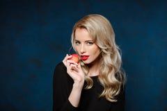 Schönes blondes Mädchen im schwarzen Kleid, das den Apfel, Kamera betrachtend hält Stockbilder