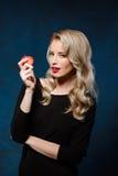 Schönes blondes Mädchen im schwarzen Kleid, das den Apfel, Kamera betrachtend hält Stockbild