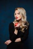 Schönes blondes Mädchen im schwarzen Kleid, das den Apfel, Kamera betrachtend hält Lizenzfreies Stockfoto