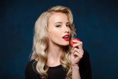 Schönes blondes Mädchen im schwarzen Kleid, das den Apfel, Kamera betrachtend hält Stockfoto