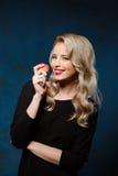 Schönes blondes Mädchen im schwarzen Kleid, das den Apfel, Kamera betrachtend hält Lizenzfreies Stockbild