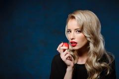 Schönes blondes Mädchen im schwarzen Kleid, das den Apfel, Kamera betrachtend hält Lizenzfreie Stockfotos