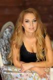 Schönes blondes Mädchen im schwarzen Kleid im Studio Stockbild