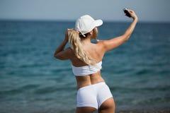 Schönes blondes Mädchen im sportwear auf dem Strand macht selfie Lizenzfreies Stockbild