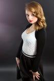Schönes blondes Mädchen im Studio auf einem schwarzen Hintergrund Lizenzfreie Stockfotos