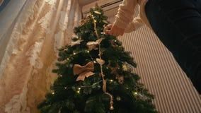 Schönes blondes Mädchen kleidet oben einen Weihnachtsbaum in einem gemütlichen Abendhaus stock footage