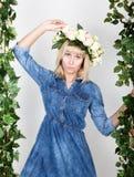 Schönes blondes Mädchen kleidete in Denim sundress, ihr Kopf ein Kranz von Blumen an Lizenzfreie Stockfotografie