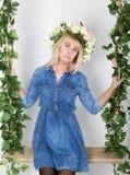 Schönes blondes Mädchen kleidete in Denim sundress, ihr Kopf ein Kranz von Blumen an Stockbild