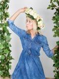 Schönes blondes Mädchen kleidete in Denim sundress, ihr Kopf ein Kranz von Blumen an Lizenzfreies Stockfoto