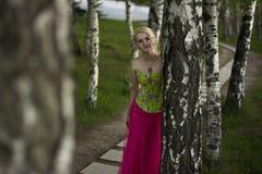 Schönes blondes Mädchen mit Bäumen, weißes Kleid Stockfotografie