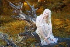 Schönes blondes Mädchen mit Bäumen, weißes Kleid Stockbilder