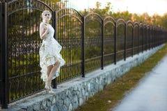 Schönes blondes Mädchen mit Bäumen, weißes Kleid Lizenzfreies Stockbild
