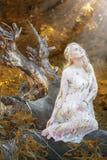 Schönes blondes Mädchen mit Bäumen, weißes Kleid Stockbild