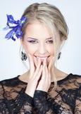 Schönes blondes Mädchen mit blauen Blumen Lizenzfreie Stockbilder