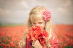 Schönes blondes Mädchen mit Blumen Lizenzfreie Stockfotografie