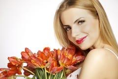 Schönes blondes Mädchen mit dem Blumenstrauß von den Tulpen lokalisiert auf einem w Stockbild