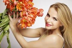Schönes blondes Mädchen mit dem Blumenstrauß von den Tulpen lokalisiert auf einem w Lizenzfreies Stockbild