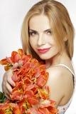 Schönes blondes Mädchen mit dem Blumenstrauß von den Tulpen lokalisiert auf einem w Stockbilder