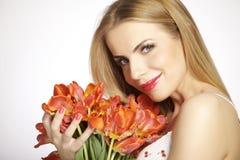Schönes blondes Mädchen mit dem Blumenstrauß von den Tulpen lokalisiert auf einem w Stockfoto