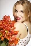 Schönes blondes Mädchen mit dem Blumenstrauß von den Tulpen lokalisiert auf einem w Lizenzfreie Stockfotos